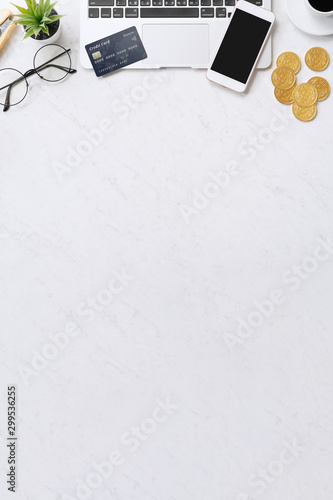 Concept of online payment with credit card with smart phone, laptop computer on office desk on clean bright marble table background, top view, flat lay - 299536255