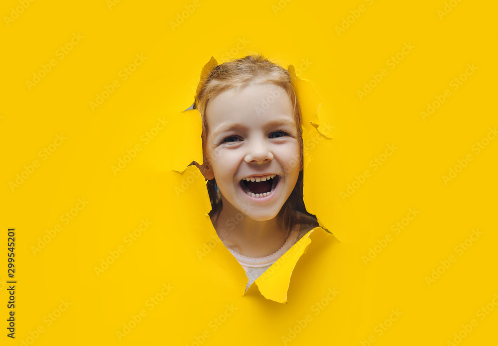 Fototapety, obrazy: The little girl smiles happily and looks up through the hole in the yellow paper. The concept of joy, good mood and expectation of surprise. Black friday, seasonal sale. Copy space, torn paper effect.