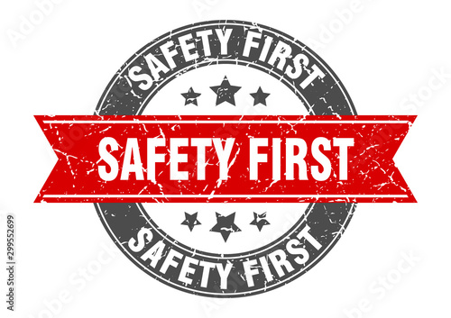 Fototapeta safety first round stamp with red ribbon. safety first