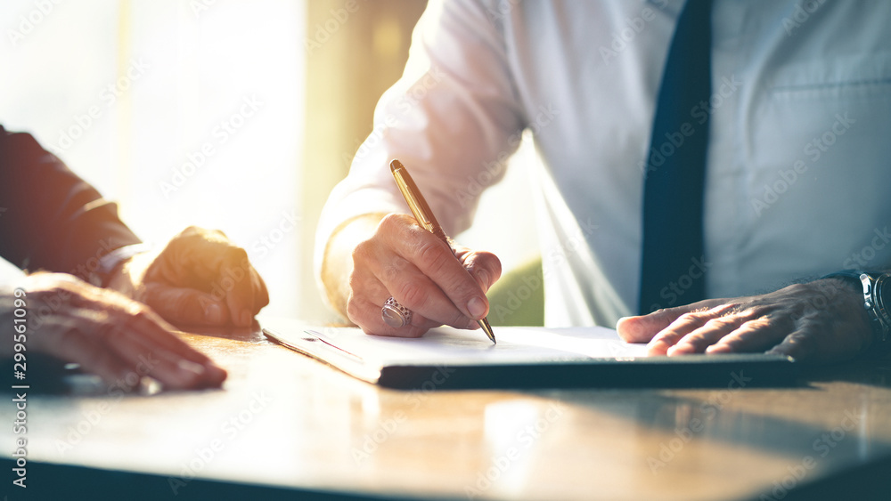 Fototapeta Closeup Businessman signing a contract investment professional document agreement on the table with pen.