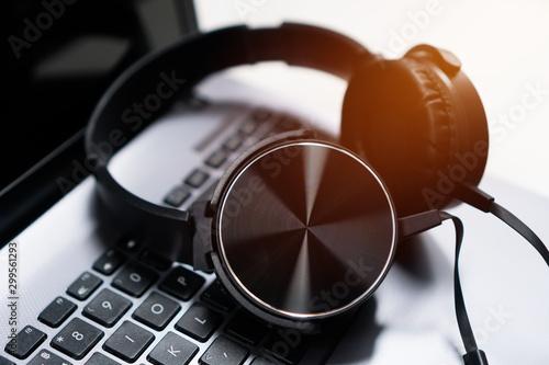 Fototapeta Headset or headphone on laptop keyboard for helpline customer on communication and hotline support call center service