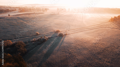 Foto auf Leinwand Lachs Aerial foggy and frozen morning countryside nature with golden autumn sunrise light and long shadows. Aerial drone view of German landscape with mist in winter times. Harz Mountains