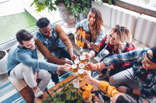 Group Of Multiracial People Having Fun Toasting Beer And Playing Guitar Laughing Together