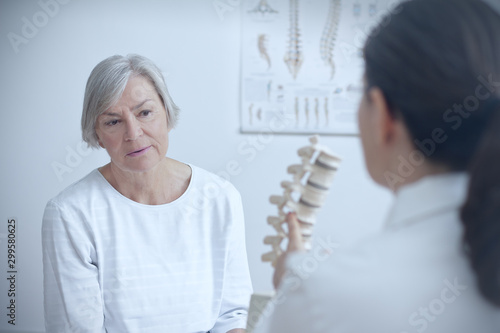 Aging and back pain concept: doctor of orthopedics showing her senior patient a degenerated disk on a backbone model Billede på lærred