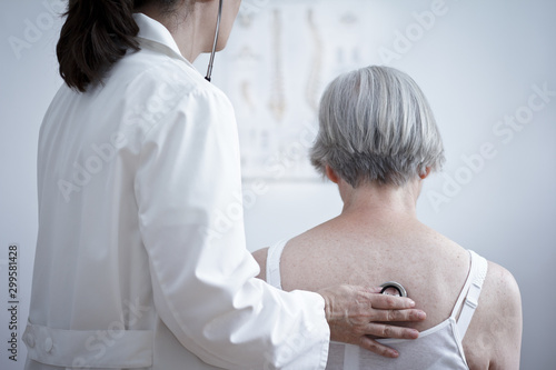 Photo Health care concept: female doctor auscultating the lungs of a senior patient with a stethoscope