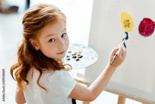 Obraz selective focus of cute redhead kid painting in art school - fototapety do salonu