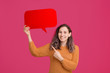 canvas print picture - Photo of cheerful young woman pointing at big red speech bubble