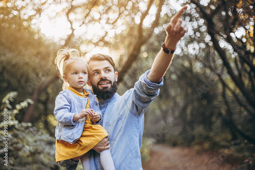 happy father and daughter playing while walking in a beautiful autumn park. Ideal weekend father with his little daughter. selective focus, noise effect