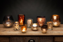 A Group Of Glass Tea Light Holders And Glowing Candles, Shot On A Wooden Table