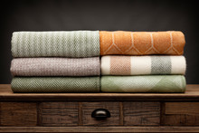 6 Luxury Throws, Folded Up And Shot On A Wooden Sideboard,  With A Grey Background
