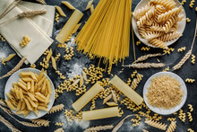 Different Types Of Italian Pasta On A Dark Wooden Rustic Background. Mixed Dry Pasta And Spaghetti. Still Life. Rustic Style. Top View.