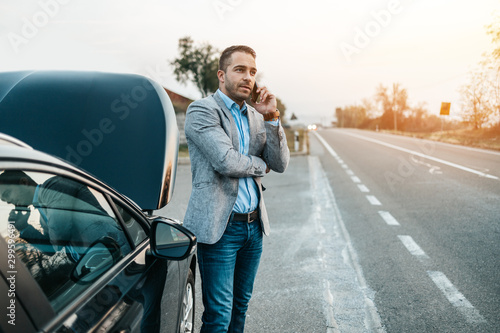 Elegant middle age business man calling towing service for help on the road Wallpaper Mural