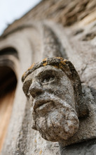 Stonework Gargoyle In The Shape Of A Kings Head Seen At The Entrance To An Old Church.