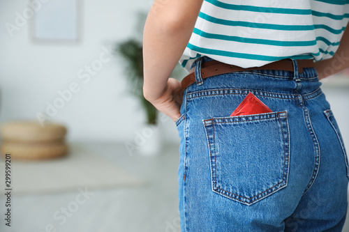 Fotomural Woman with condom in pocket of her jeans indoors, closeup