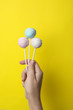canvas print picture - Woman holding sweet cake pops on yellow background, closeup