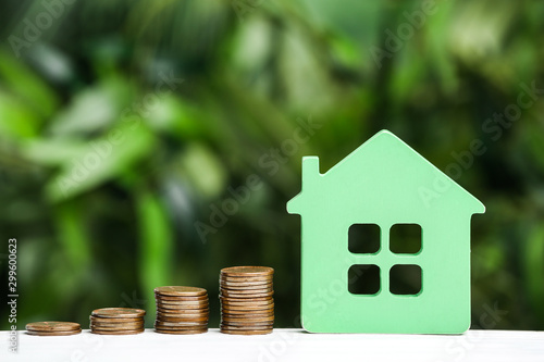 Photo Green house model and coins on white wooden table against blurred background