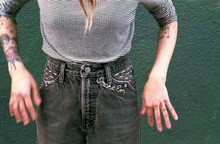 Midsection Of Woman Wearing Jeans Embroidered With Cigarettes