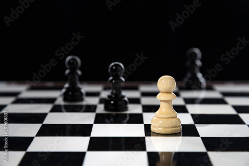 Canvas Print A white pawn stands on a chessboard against black pawns