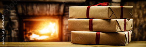 Fotografia  Winter christmas gifts on desk and fireplace background.