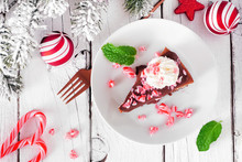 Christmas Candy Cane Chocolate Cheesecake. Top View Table Scene Against A White Wood Background.