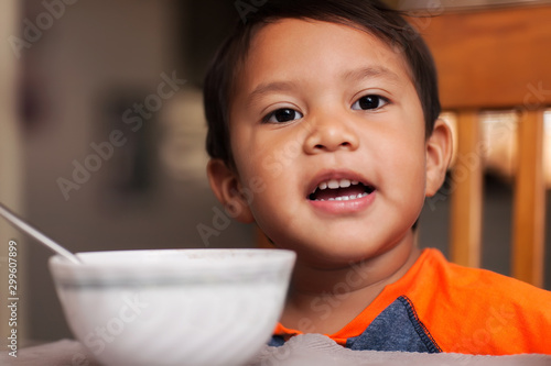 A hispanic boy at the dinner table with a bowl, spoon and ready to eat breakfast Canvas Print