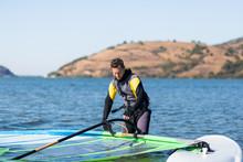Sportsman Preparing His Windsurfing Equipment In Shallow Water.
