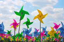 Colourful Children's Pinwheels In The Blue Sky With Clouds