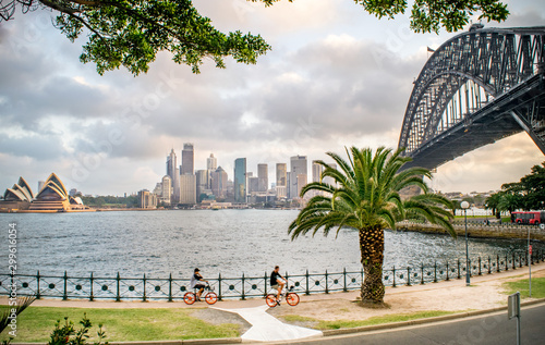 Wide Shot of Tourists Biking along Sydney Harbour, with a view of the Sydney Skyline, Milsons Point, Waterfront, Sydney Harbour Bridge, and Opera House on a Summer Evening - Sydney, Australia  © Nate Hovee