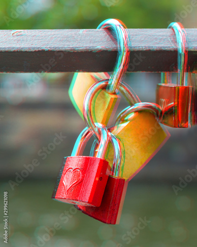 Locks on metal bridge railing over green water, 3D anaglyph effect Wallpaper Mural