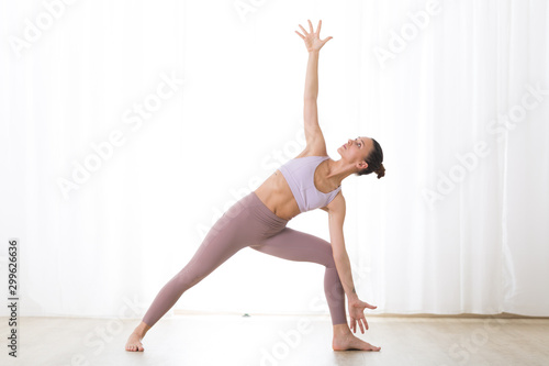 Portrait of gorgeous active sporty young woman practicing yoga in studio Wallpaper Mural
