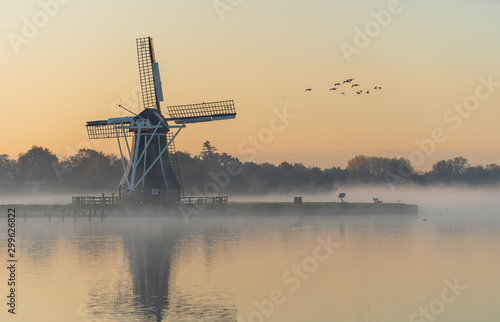 Photo Nature awakens at a traditional Dutch windmill during a foggy sunrise