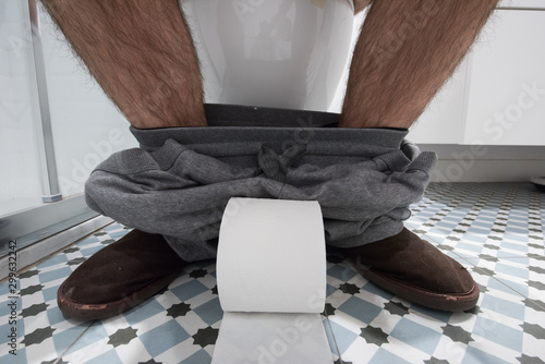 Fotografía Pies de un hombre en el baño con papel higiénico