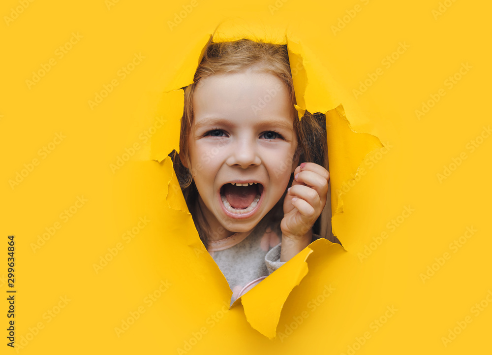 Fototapety, obrazy: The little red-haired girl screams desperately from fear and fright, peering out from yellow paper in the center. The concept of horror and surprise. Torn background, copy space.