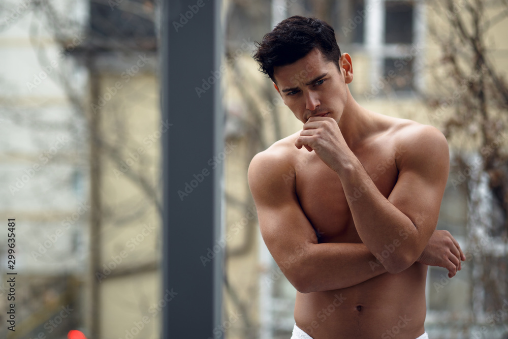 Fototapeta Handsome. shirtless muscular young man in bathroom towel, standing on the balcony, isolated on street background.