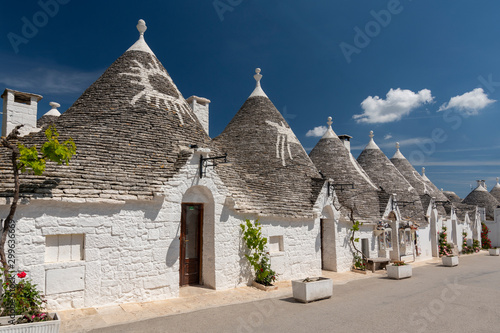 Row of traditional whitewashed trulli houses with conical roofs in Alberobello, Puglia, southern Italy Canvas Print
