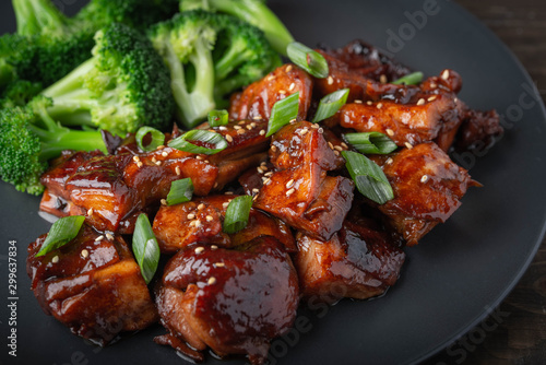 teriyaki chicken and broccoli on black plate Canvas Print