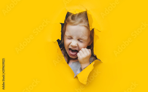 Photo The little red-haired girl screams and cry desperately from fear and fright, peering out from yellow paper in the center