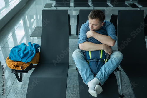 Young man at the airport waiting for his plane looking at the window Tableau sur Toile