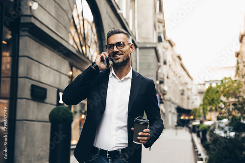 obraz dibond City walk. Technology. Coffee break. Business. Handsome man in suit is talking on the mobile phone, holding a cup of coffee and smiling while walking outdoors