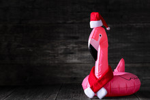 Inflatable Pink Flamingo In Santa Claus Hat And Red Scarf On Wooden Rustic Background