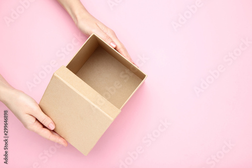 Obraz Female hands opening brown gift box on pink background - fototapety do salonu