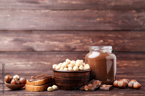Fototapeta  Bread with melted chocolate and peeled hazelnuts on brown wooden table
