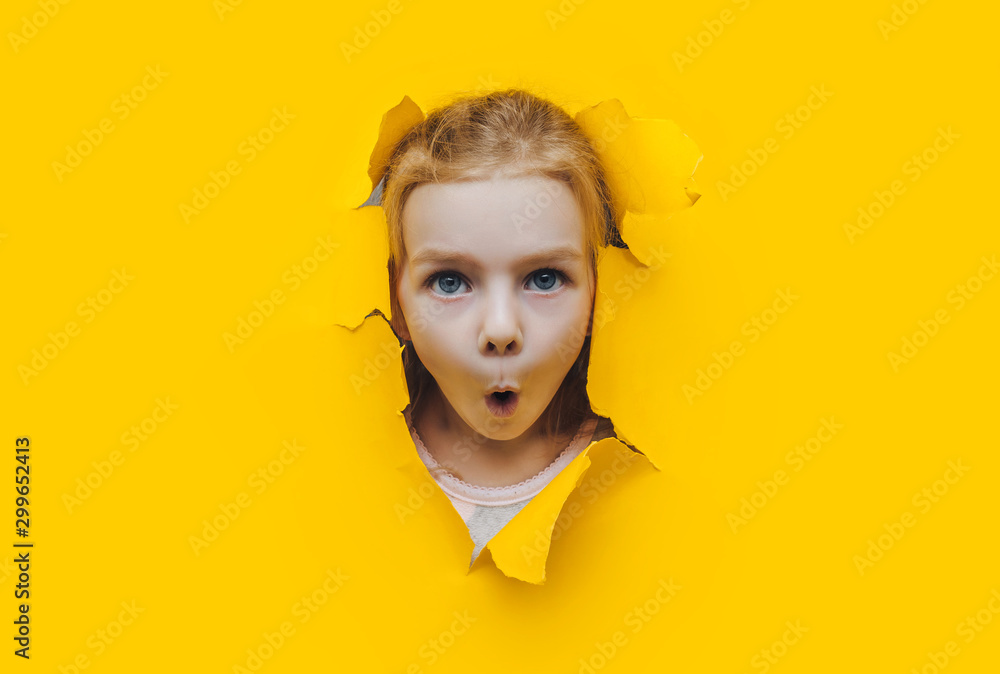 Fototapeta Funny red-haired child girl peeping through hole on yellow paper. The concept of surprise, fear, fright, joyful mood from what he saw. Discounts, sales, surprise. Copy space.