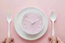 Pink Clock On White Plate And Hands Holding Spoon And Fork, Intermittent Fasting Concept, Ketogenic Diet, Weight Loss, Skip Meal, New Year 2020 Health  Diet  Resolution