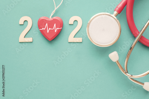 fototapeta na lodówkę 2020 wooden number with red stethoscope. Happy New Year for heart health and medical concept, life insurance business