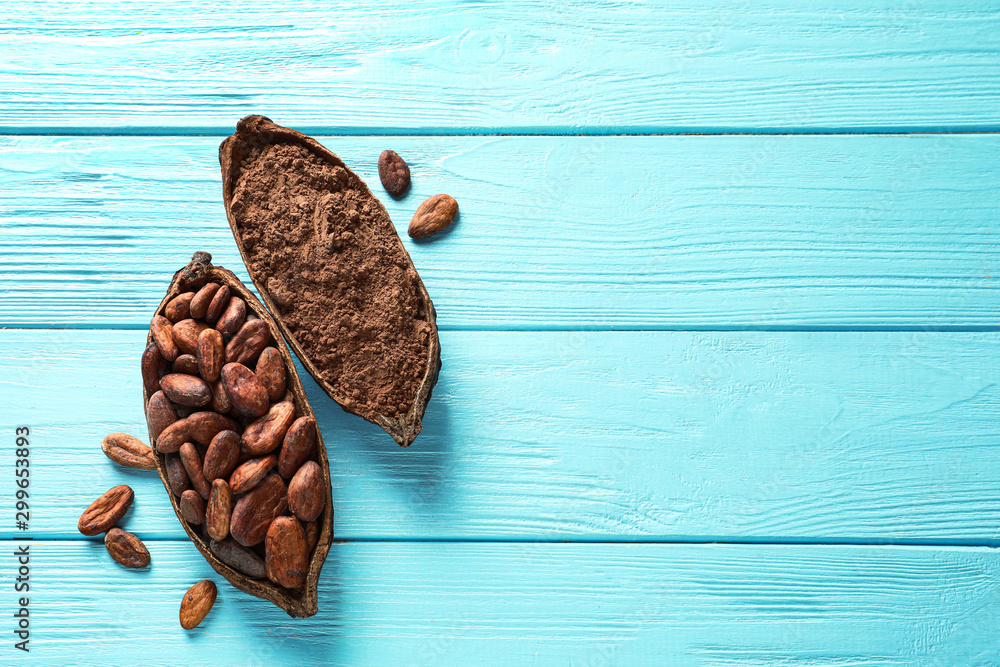 Fototapety, obrazy: Halves of cocoa pod with beans and powder on blue wooden table, top view. Space for text