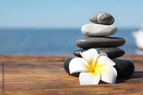 Stack of stones and flower on wooden pier near sea, space for text. Zen concept