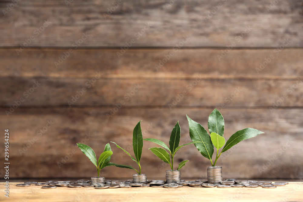 Fototapety, obrazy: Stacked coins and young green plants on wooden table, space for text