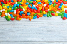 Colorful Jelly Beans On White Wooden Background, Flat Lay. Space For Text