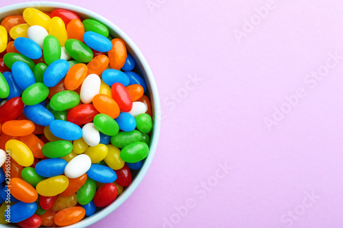 Bowl with colorful jelly beans on lilac background, top view. Space for text